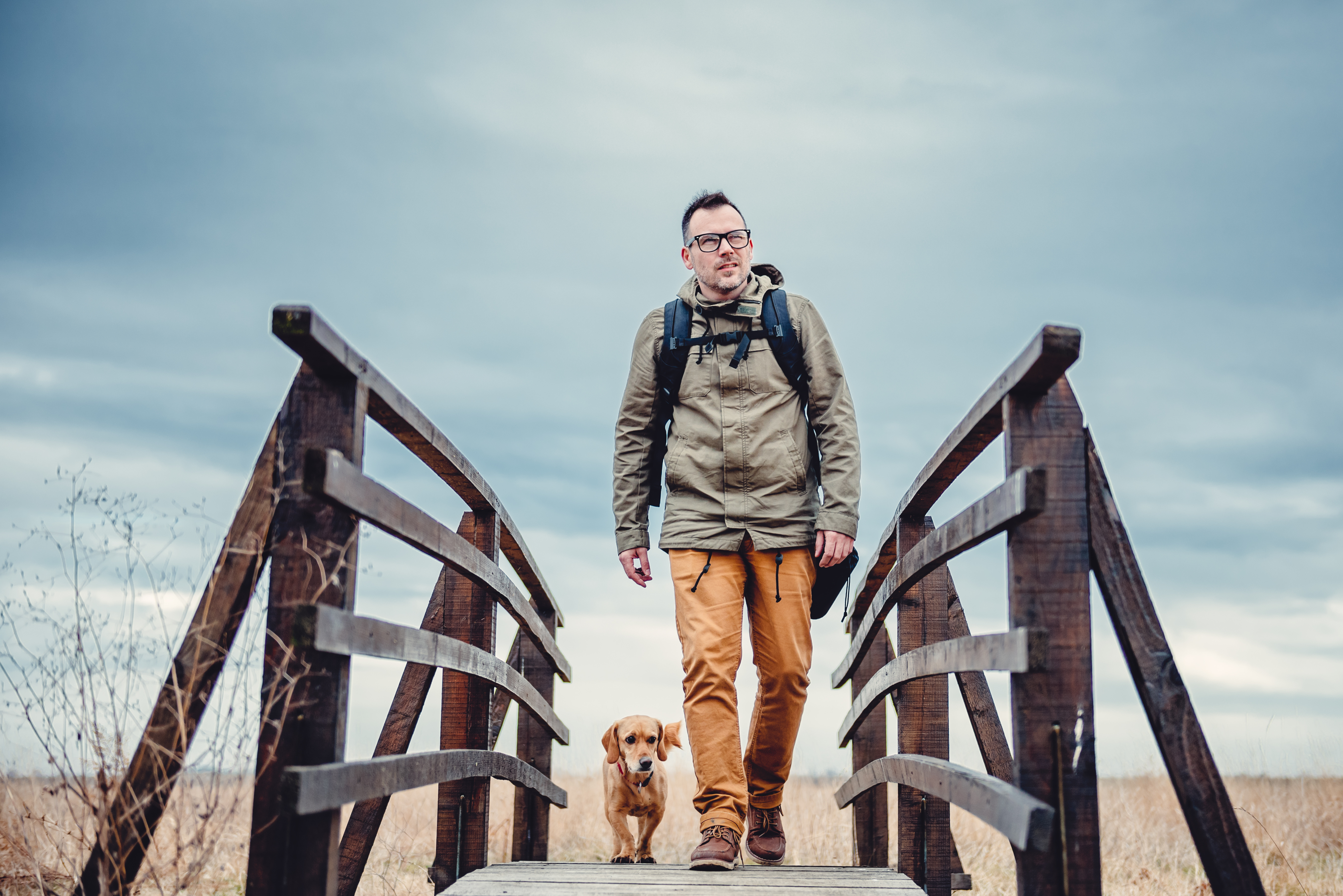Hiker And Dog On Wooden Bridge